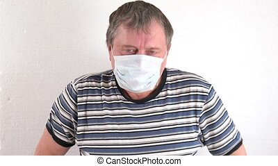 Coughing man wears a medical mask breaks image covid 19, throws the piece of paper and takes off his protective mask. The restoration ended the quarantine