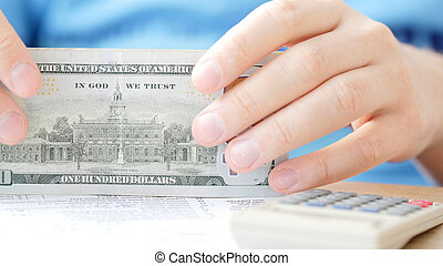 Man counting dollars and filling tax form.