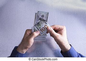 Man counting or paying out 100 dollar bills in a financial and monetary concept viewed from above with only his hands visible