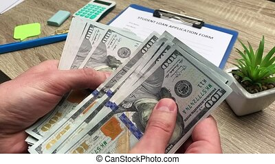 Man counts 100 dollars banknote received on a student loan