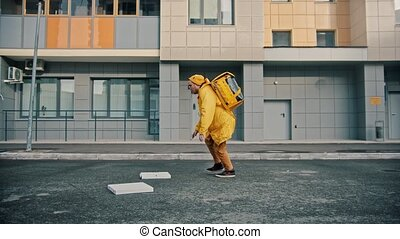 Man courier in yellow clothes delivers food drops pizza boxes on the floor and continue delivering. Mid shot