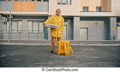 Man courier in yellow clothes delivers food - holding pizza ...