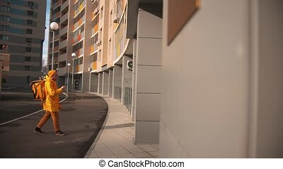 Man courier in yellow clothes delivers food - standing near ...
