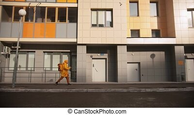 Man courier in yellow clothes delivers food - walking near ...