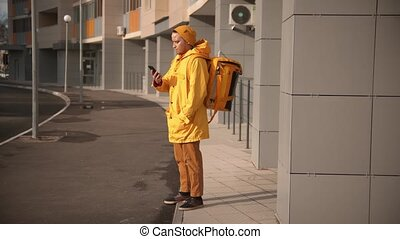 Man courier in yellow clothes delivers food - walks out the ...