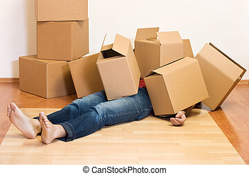 Man covered in cardboard boxes - moving concept - Man...