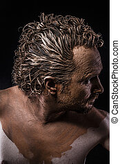 man covered in mud, naked, in profile, ancient warrior