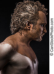 man covered in mud, naked, in profile