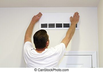 Man Covering Air Vent - Male placing a paper cover over part...