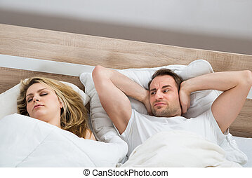 Man Covering Ears While Woman Sleeping
