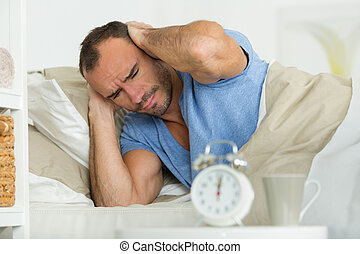 man covering his ears beside alarm clock on bed