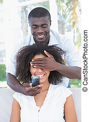 Man covering the eyes of his girlfriend while preparing proposal