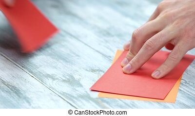 Man creating origami close up. Male hands dividing paper...