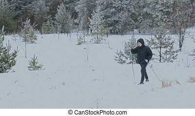 Man Cross-Country Skiing Alone in Nature