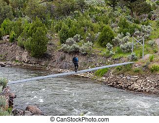 Man Crosses Footbridge Over Rushing River