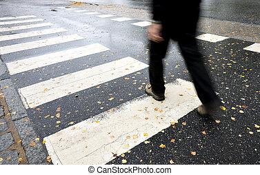 Man crossing street - Man in black crossing street on wet...