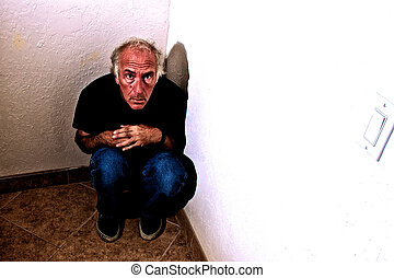 man crouching in corner scared