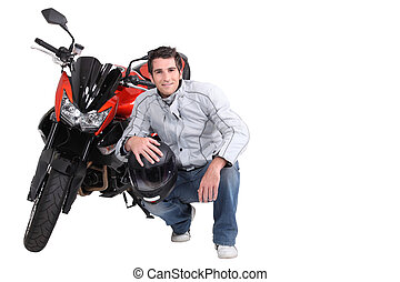 Man crouching next to motorcycle
