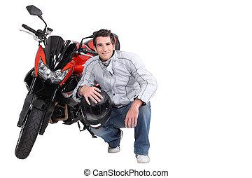 Man crouching next to motorcycle