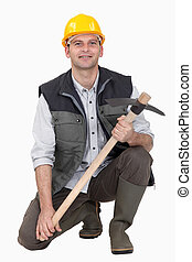 Man crouching with pick-ax