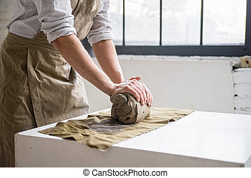 Man crumples piece of white clay for sculpting