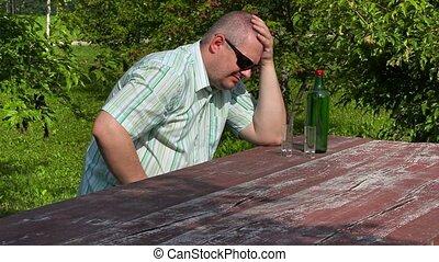 Man crying near bottle of alcohol