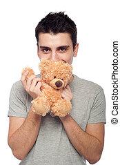 Man cuddling teddy bear - lovely portrait of a young man...