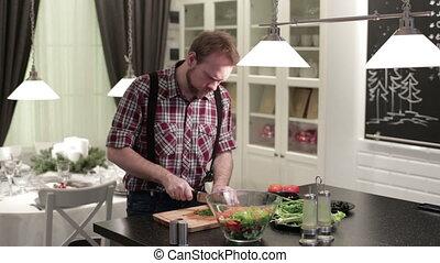 Man cut green onions on a wooden board