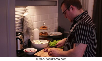 Man cut red onions on a wooden cutting board