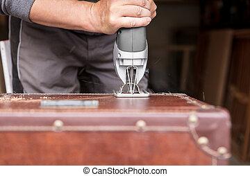 Man cuts a cutout into a chest