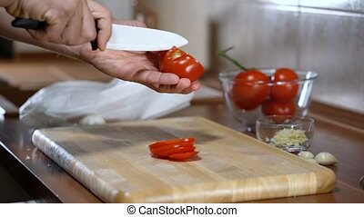 man cuts a tomato for cooking bruschetta, close up