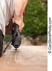 Man cuts cutout into a countertop