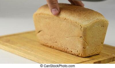 man cuts fresh crisp bread with a knife - man cuts fresh...