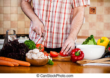 Man cuts fresh spring vegetables on the kitchen table, ...