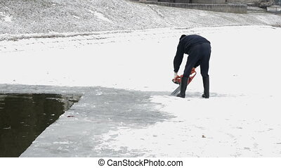 Man Cuts Ice With Chainsaw on the Frozen Lake