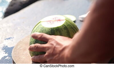 man cuts large red water melon with big knife