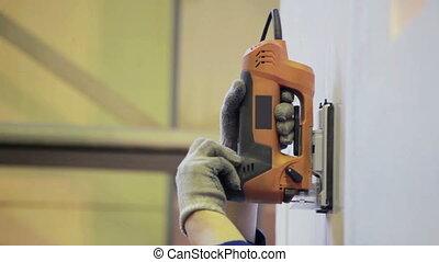 Man cuts metal by electric jigsaw