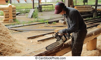 Man cuts off beam chainsaw for future home. Construction works with a wooden structure