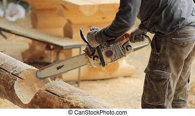 Man cuts off beam chainsaw for future home. Construction works with a wooden structure. Close up