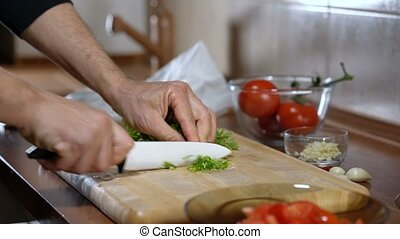 man cuts parsley for cooking bruschetta, close up