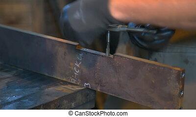 Man cuts thread. Man cuts tapping in a metal plate