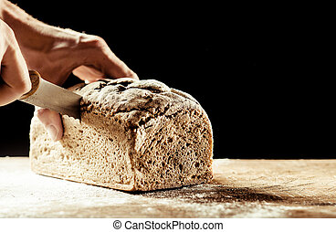 Man cutting a homemade loaf of wholegrain bread