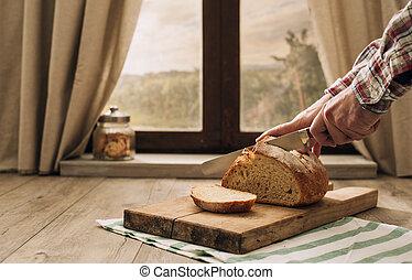 Man cutting a loaf of fresh bread