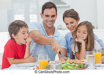 Man cutting a pizza for his family