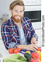 man cutting a tomato on cutting board