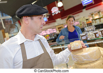 man cutting a wheel of cheese