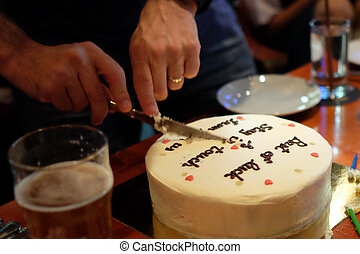 Man cutting birthday cake in dimmed light pub, birthday party concept