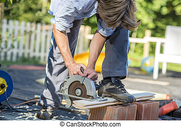 Man cutting boards with a circular saw
