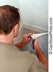 Man cutting carpet to fit a corner