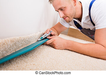 Man Cutting Carpet With Cutter - Close-up Of A Young...